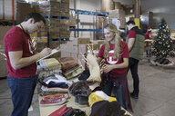 Volunteers sorting Christmas clothing for clothing drive in warehouse - HEROF20290