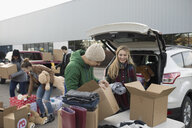 Young adult volunteers packing donations in parking lot - HEROF20299