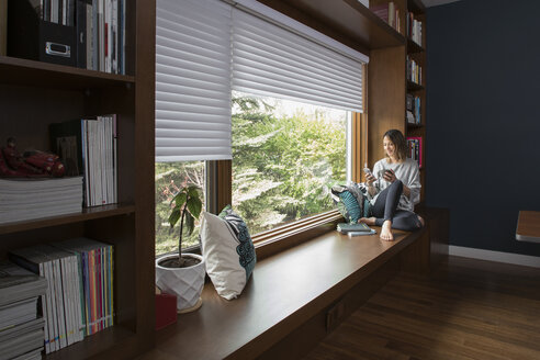 Woman texting with smart phone at window seat in home office - HEROF20326