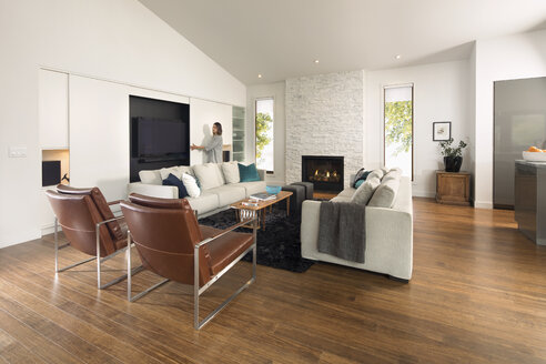 Woman opening TV cabinet in home showcase living room - HEROF20329
