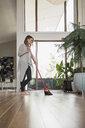 Woman sweeping hardwood floors with broom - HEROF20344