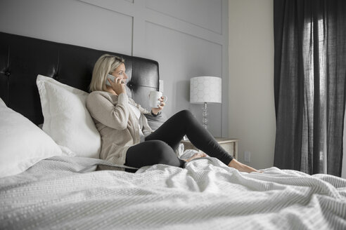 Woman relaxing, drinking coffee and talking on cell phone in bed - HEROF20350