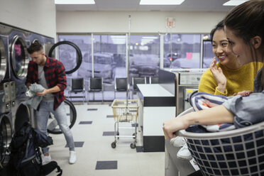 Young women friends checking out young man doing laundry at laundromat - HEROF20380