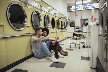 Young couple sitting and talking while waiting for laundry at laundromat - HEROF20386