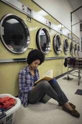 Young woman reading book, waiting for laundry at laundromat - HEROF20389