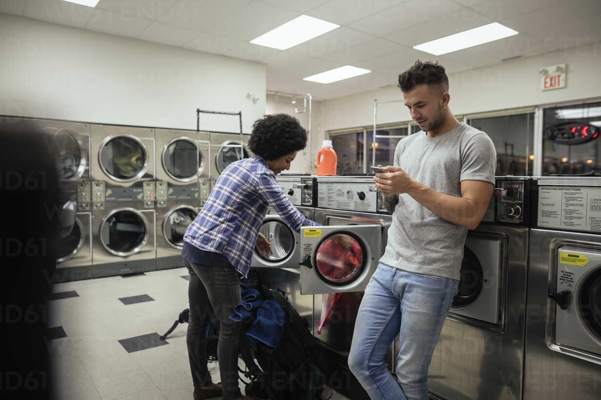 Young couple doing laundry at laundromat - HEROF20392 - Hero Images/Westend61