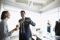 Happy businessman celebrating, pouring champagne for businesswoman in conference room - HEROF20464