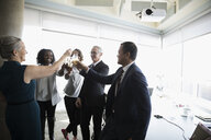 Happy business people celebrating, toasting champagne glasses in conference room - HEROF20467