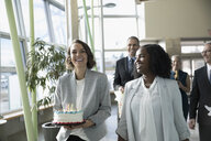 Happy businesswomen carrying birthday cake in office - HEROF20470