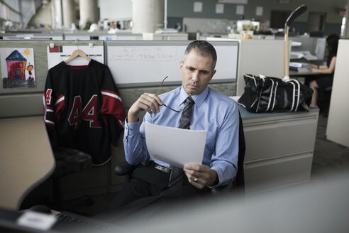 Focused mature businessman reviewing paperwork in office cubicle with hockey jersey and gym bag - HEROF20482