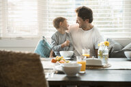 Happy father and son eating breakfast in breakfast nook - HEROF20530