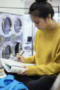 Focused female college student studying, waiting for laundry at laundromat - HEROF20551