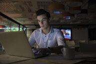 Focused, dedicated businessman working late at laptop in dark office - HEROF20581