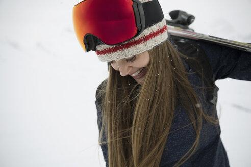 Happy female skier looking down at snow - HEROF20584