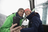 Happy mature couple skiers taking selfie with camera phone on gondola - HEROF20587