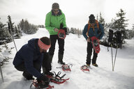 Friends putting on snowshoes in snow - HEROF20590