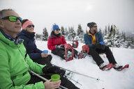 Friends enjoying coffee, taking a break from snowshoeing in snow - HEROF20605