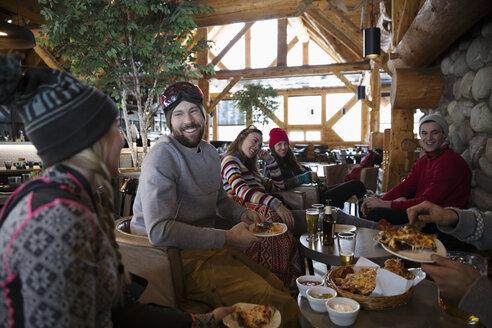 Friends enjoying apres-ski beer and snacks in ski resort lodge - HEROF20617