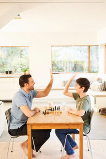 Boy and father playing chess at living room table, high fiving - CUF48518
