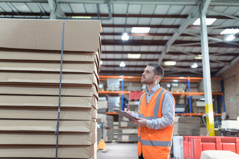 Worker inspecting boxes in cardboard box factory - CUF48572