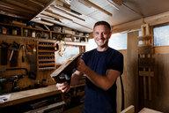 Craftsman holding wood plane in workshop - CUF48593