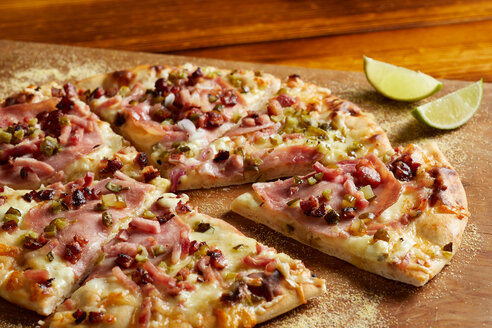 Cuban ham & swiss pizza with lime on chopping board - CUF48638