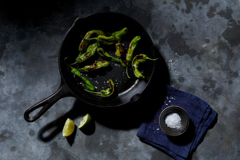 Skillet with saute shishito peppers with lime and sea salt, overhead view - CUF48644
