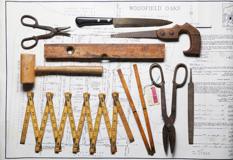 Variety of vintage hand tools on property map, overhead view - CUF48650