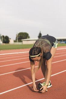 Female athlete doing warm-up exercises on tartan track - ACPF00441