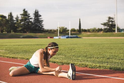 Female athlete doing warm-up exercises on tartan track - ACPF00444