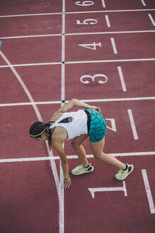 Top view of female runner in starting position on tartan track - ACPF00447