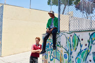Two young men waiting by park fence, Los Angeles, California, USA - CUF48692