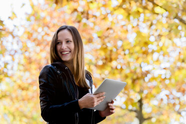 Young woman using digital tablet in park - CUF48827