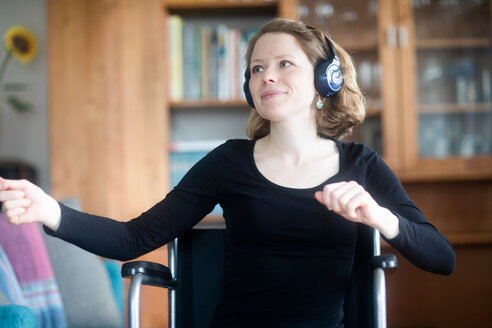 Woman in wheelchair dancing to music on headphones - CUF48950