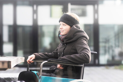 Woman in wheelchair in street - CUF48953