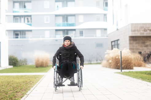 Woman in wheelchair in residential area - CUF48959