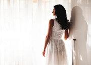 Woman in summer dress beside window - CUF48995