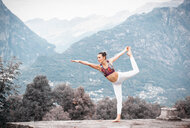Woman practicing yoga, balancing on one leg in mountain landscape, Domodossola, Piemonte, Italy - CUF49004