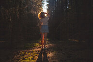 Woman looking up from dark sunlit forest, rear view - CUF49016