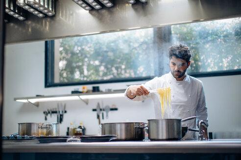 Chef cooking pasta in kitchen - CUF49028