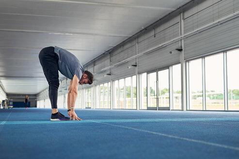 Runner stretching on indoor running track - CUF49049