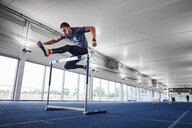 Athlete jumping over hurdle on indoor running track - CUF49067