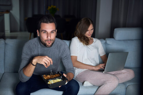 Young couple sitting on sofa in evening eating takeaway and using laptop - CUF49103