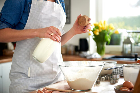 Woman pouring milk into mixing bowl in kitchen - CUF49115
