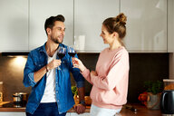 Couple talking and drinking red wine in kitchen - CUF49127