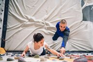 Climber guiding friend on climbing wall - CUF49133
