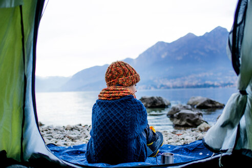 Boy sitting on blanket by tent, rear view, Lake Como, Onno, Lombardy, Italy - CUF49157