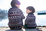 Boy and toddler brother in matching sweaters talking on pier, Lake Como, Lecco, Lombardy, Italy - CUF49220
