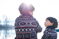 Boy and toddler brother in matching sweaters talking on lakeside, Lake Como, Lecco, Lombardy, Italy - CUF49223