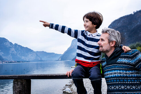 Boy and father pointing from lakeside pier, Lake Como, Onno, Lombardy, Italy - CUF49226